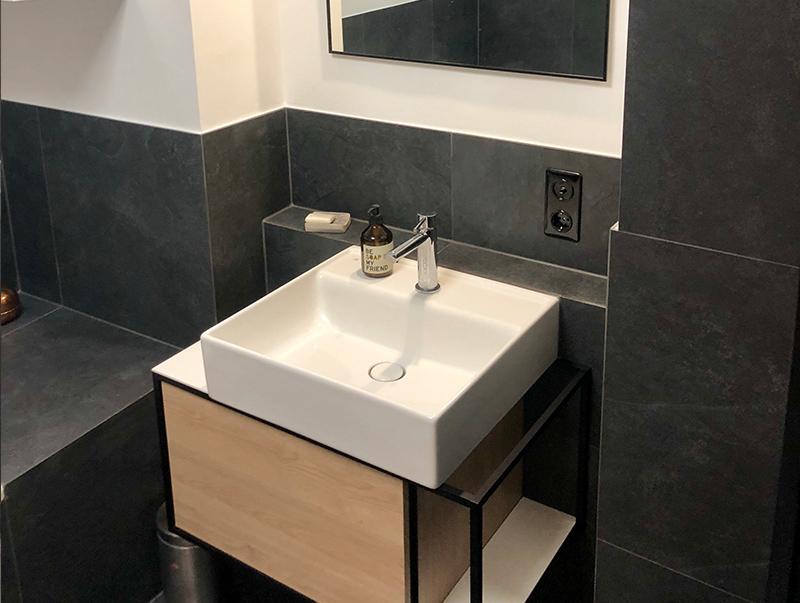 Modernes Waschbecken mit dunklen Fliesen